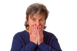 Seniorin hält sich den Mund zu - freigestellt auf weissem Hintergrund