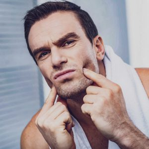 Teeth pain. Close up of serious unemotional man with a towel around his neck pressing his fingers on his cheeks while having unpleasant mood